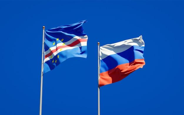 Красивые национальные государственные флаги россии и кабо-верде вместе на голубом небе. 3d изображение