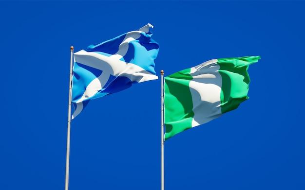 Красивые национальные государственные флаги шотландии и нигерии вместе на голубом небе