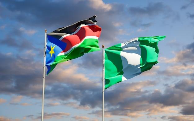 Красивые национальные государственные флаги южного судана и нигерии вместе на голубом небе