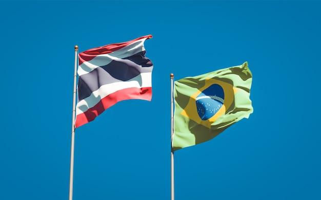 Красивые национальные государственные флаги таиланда и бразилии вместе на голубом небе