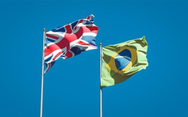 Красивые национальные государственные флаги великобритании и бразилии вместе на голубом небе