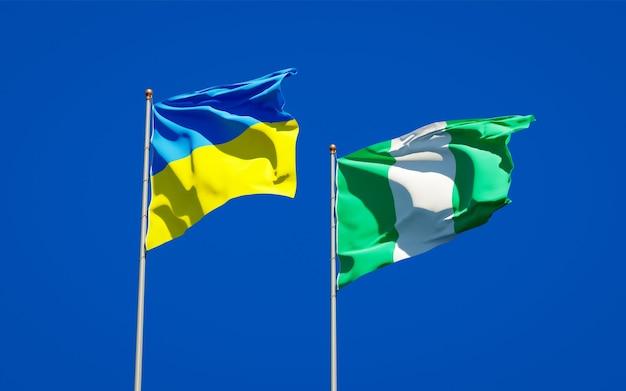 Красивые национальные государственные флаги украины и нигерии вместе на голубом небе