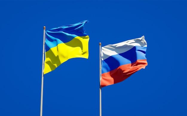 Красивые национальные государственные флаги украины и россии вместе на голубом небе. 3d изображение