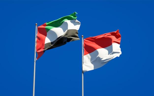 Красивые национальные государственные флаги объединенных арабских эмиратов, оаэ и индонезии вместе на голубом небе
