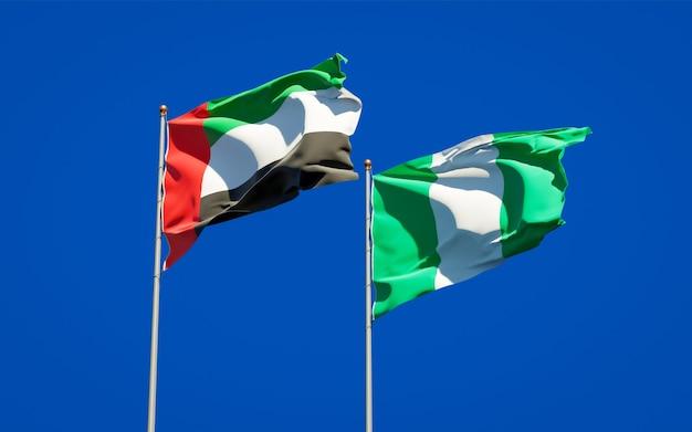 Красивые национальные государственные флаги объединенных арабских эмиратов, оаэ и нигерии вместе на голубом небе