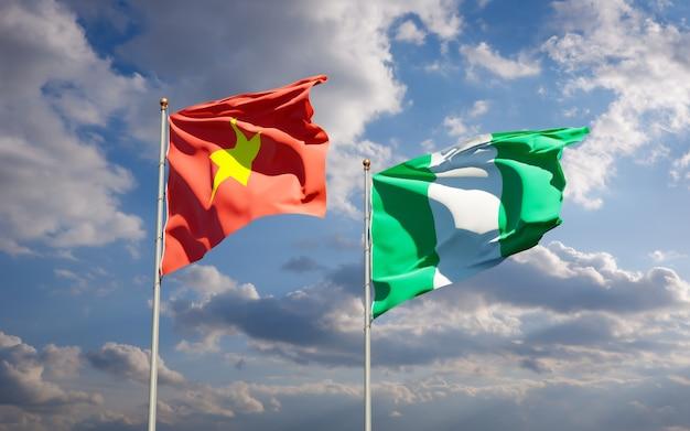 Красивые национальные государственные флаги вьетнама и нигерии вместе на голубом небе