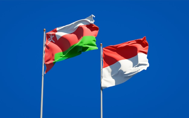 Beautiful national state flags of oman and indonesia together on blue sky