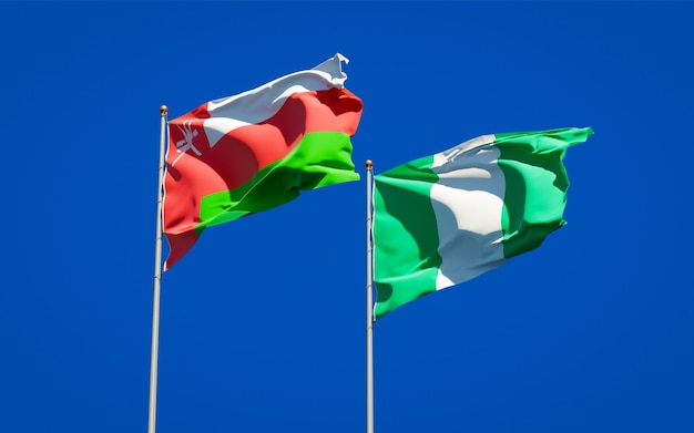 Beautiful national state flags of oman and nigeria together on blue sky