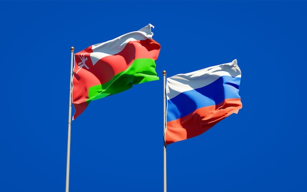 Beautiful national state flags of oman and russia together on blue sky. 3d artwork