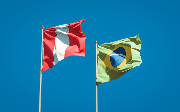 Beautiful national state flags of peru and brasil together on blue sky