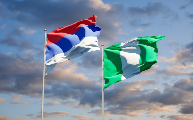 Beautiful national state flags of republika srpska and nigeria together on blue sky