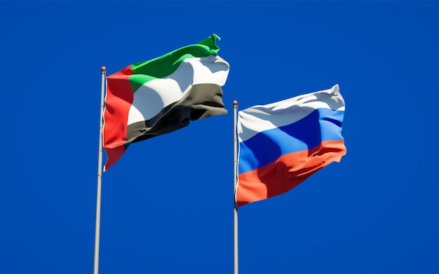 Beautiful national state flags of united arab emirates uae and russia together on blue sky. 3d artwork