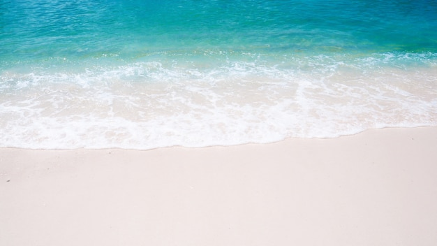 Beautiful natural background on white sand beach green sea water and wave in summer