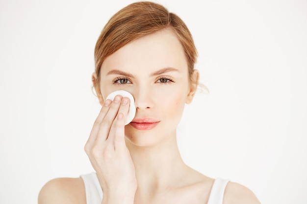Beautiful natural blonde girl cleaning face with cotton sponge smiling . cosmetology and spa.