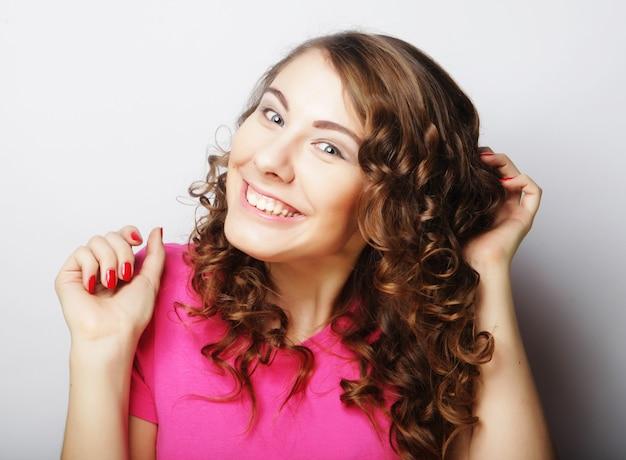 Красивая женщина естественного макияжа с длинными светлыми волосами в вьющейся прическе, улыбаясь в камеру