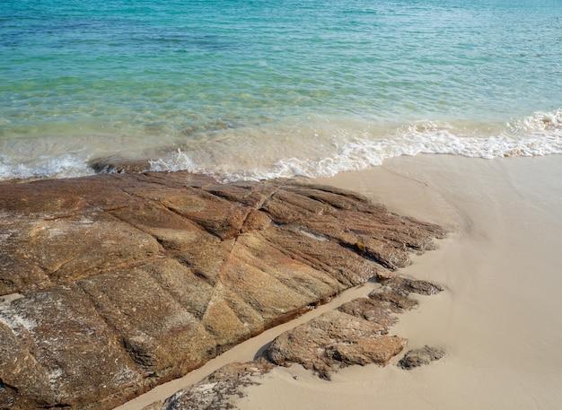 Красивые природные скалы на песчаном пляже и бирюзовые морские волны.