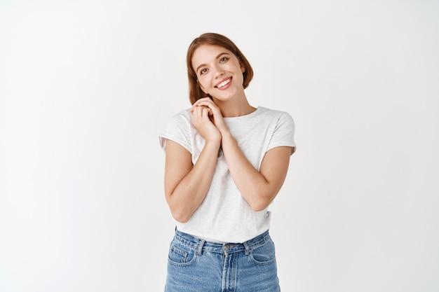 Красивая натуральная женщина любуется чем-то, держась за руки возле лица и глядя на симпатичную вещь, стоящую на белой стене