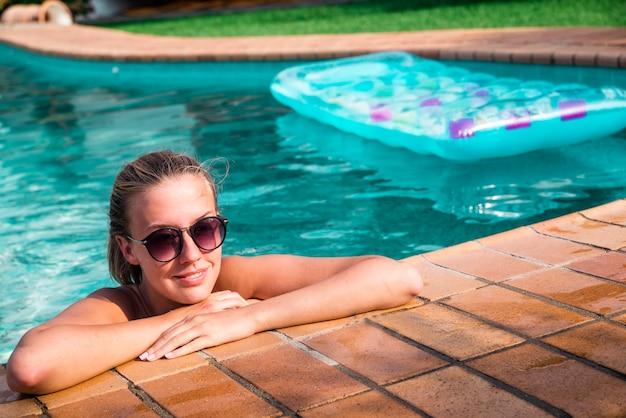 Bella donna naturale sorridente in piscina sulle vacanze estive. giovane modello femminile in bikini.