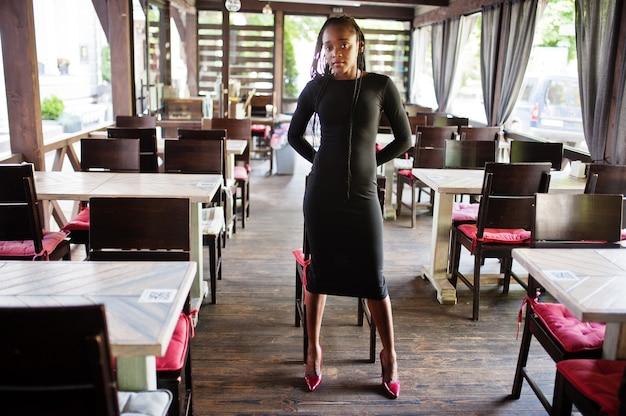 夏のテラスカフェでポーズをとった、アフロヘアの美しい自然な若いアフリカの女性は黒いドレスを着ています。