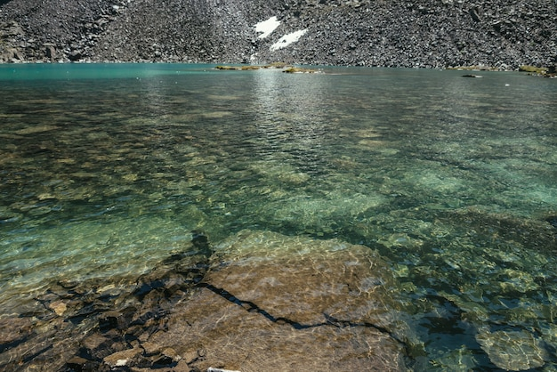 Beautiful nature background of stony bottom in turquoise transparent water of glacial lake in sunlight. sunny backdrop with many stones in green clear water of glacier lake. texture of mountain lake.