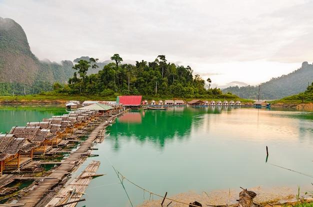 Красивый природный пейзаж с зелеными горами и бамбуковой хижиной на озере, плавающей в ряд в винтажном загородном стиле курорта, мирным утром, путешествие в азию в национальном парке кхао сок, сураттани, таиланд