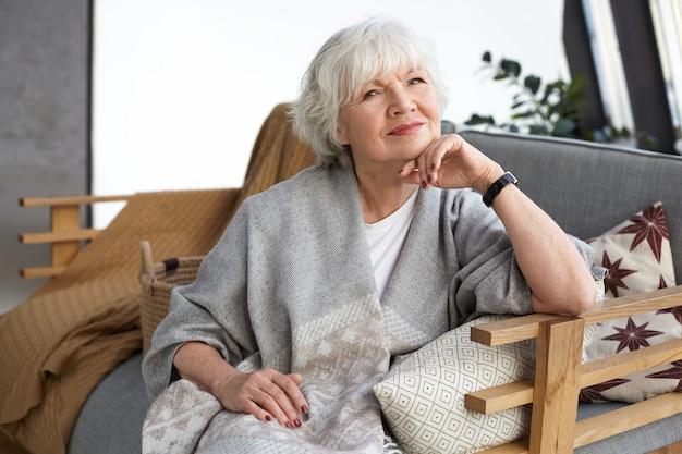 Красивая аккуратная шестидесятилетняя бабушка в широком сером шарфе и наручных часах удобно отдыхает на диване в гостиной, счастливо улыбается, ожидая прихода сына и внуков