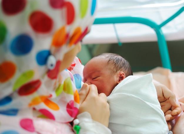 彼の母親の手で美しい生まれたばかりの赤ちゃん。
