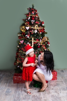 Beautiful new year mother and daughter enjoy the christmas tree. enjoying winter family new year holidays