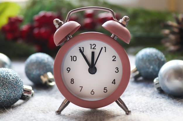 Красивая новогодняя открытка. розовые часы на праздничном размытом фоне.
