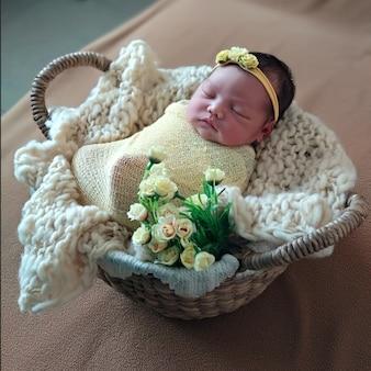 아름다운 신생아 소녀는 천으로 싸여 있고 바구니에서 자고 있는 니트 모자를 쓰고 있습니다.