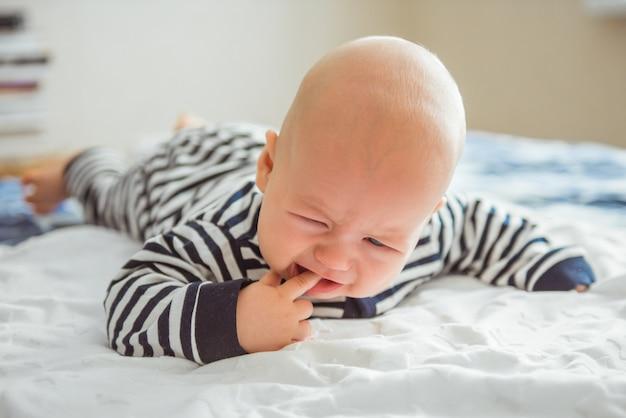 彼のベッドで横になっていると泣いている美しい生まれたばかりの赤ちゃん