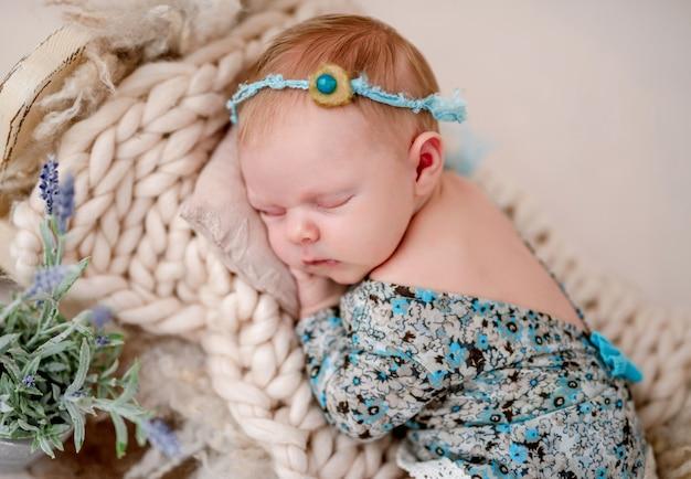 小さなベッドで寝ている美しい新生児の女の赤ちゃん