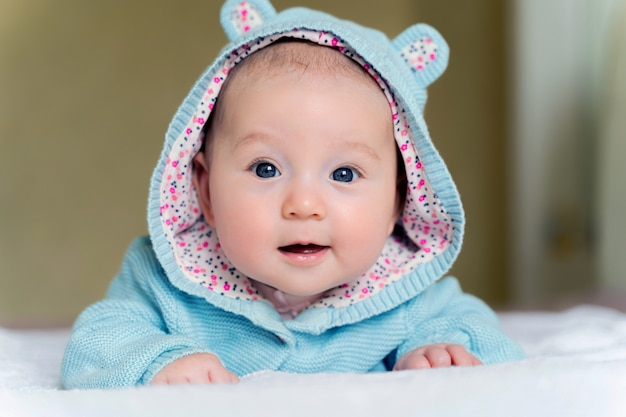 Beautiful newborn blue eyed girl lies on her tummy and smiles