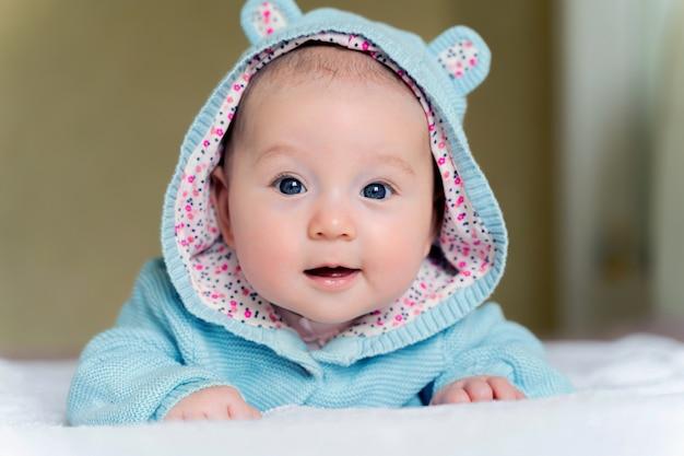 美しい新生児の青い目をした少女は彼女のおなかと笑顔にあります。