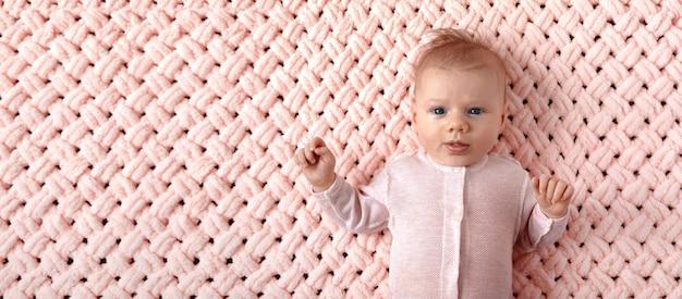 ピンクのニット格子縞の美しい新生児の女の子