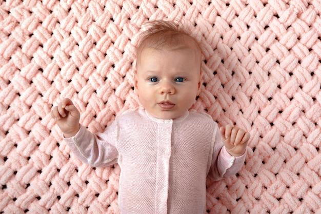ピンクのニット格子縞の美しい新生児の女の子。