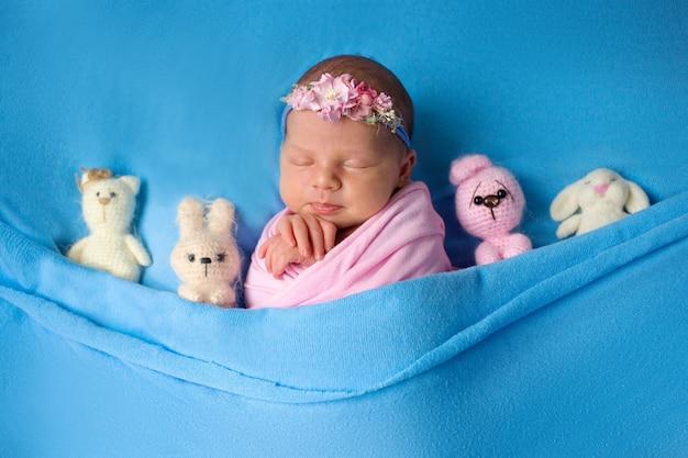 ニットのおもちゃで眠っている美しい新生児