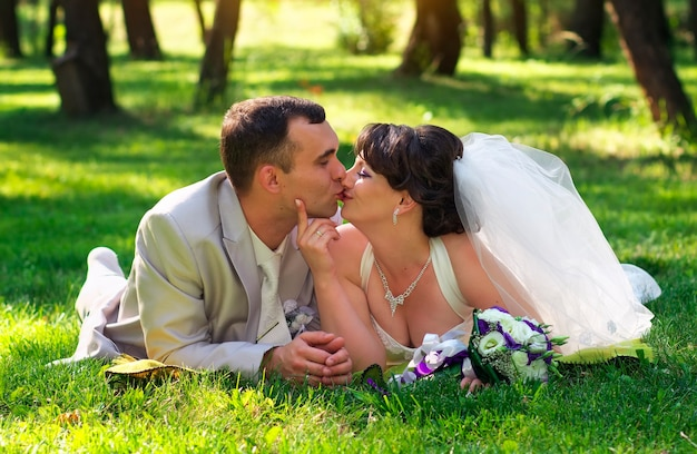 公園で草の上に横たわってキスをしている美しい新婚夫婦