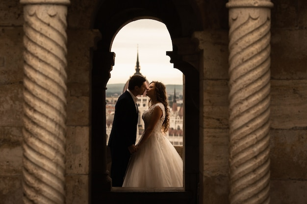 Beautiful newlywed brunette bride in white wedding dress and the groom in black suit posing near old column building in budapest