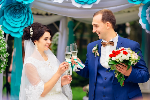 Beautiful newlywed couple during wedding ceremony clinking glass