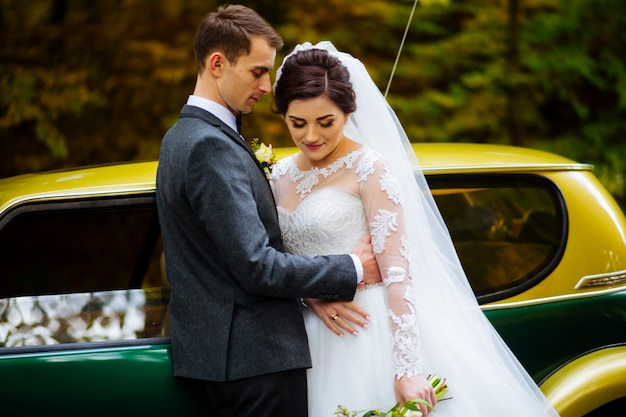 Beautiful newlywed couple posing near retro red car