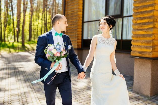 아름 다운 신혼 부부, 신부 및 신랑 걷기