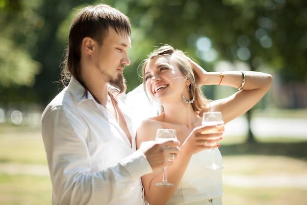 야외에서 샴페인을 마시는 아름 다운 신혼 부부