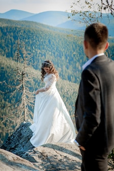 Beautiful newlyweds hugging against the backdrop of rocks and mountains. stylish bride and beautiful bride are standing on the cliff. wedding portrait. family photo