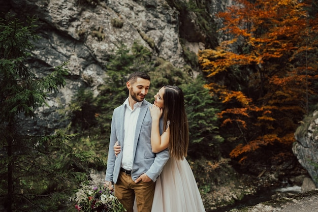 岩、石、木々を背景に抱き締める美しい新婚夫婦。
