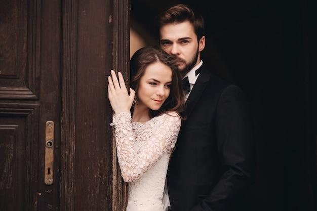 Beautiful newlyweds hugging near the ancient door