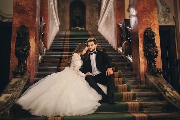 Красивые молодожены обнимаются на лестнице старинного дома. свадебный портрет стильного жениха и молодой невесты внутри.