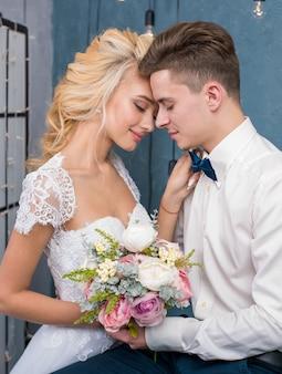 Красивые молодожены сидят и держатся за руки в серой студии. портрет жениха и невесты в кружевном платье. нежный свадебный портрет.