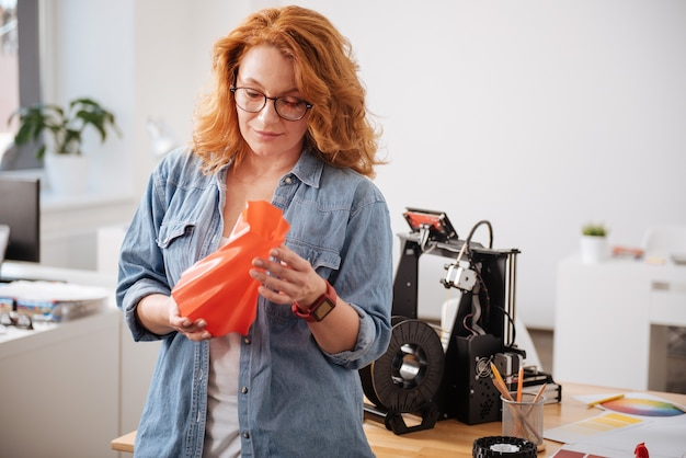 Beautiful nice attractive woman holding a 3d printed vase and looking at it while designing household objects
