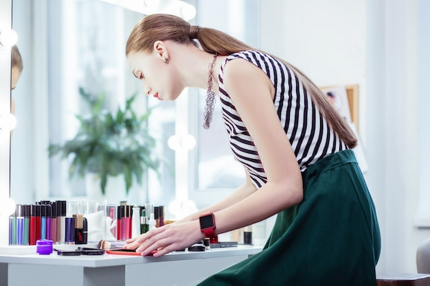 Beautiful nice woman looking at her cosmetics while wanting to put makeup